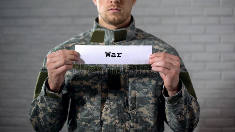 Oorlogswoord op teken in handen van mannelijke militair wordt geschreven, gewapend conflict, slachtoffers dat stock afbeelding