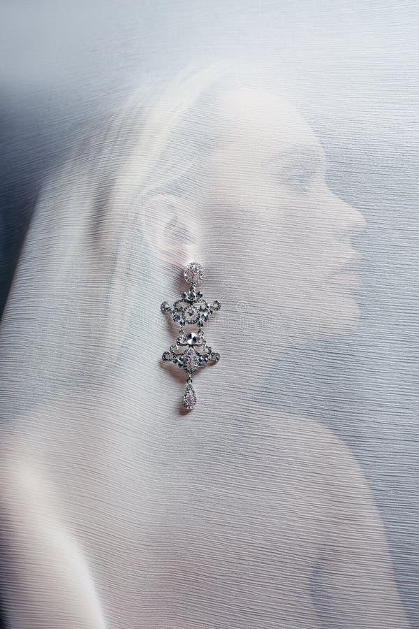 Oorringen en juwelen in het oor van een sexy die vrouw door een transparante stof wordt opgenomen Perfect blondemeisje, schittere royalty-vrije stock fotografie