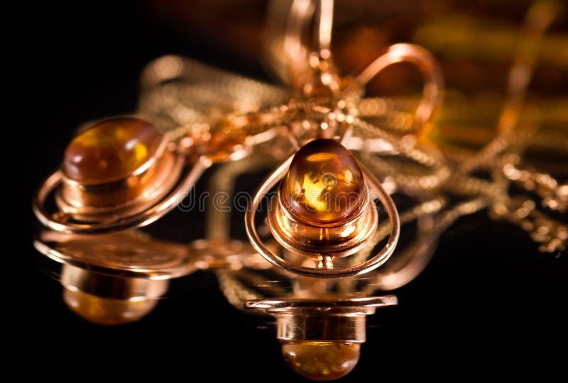 Oorringen met kostbare amber stock fotografie