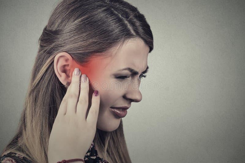 oorsuizing Zieke jonge vrouw die oorpijn hebben royalty-vrije stock fotografie