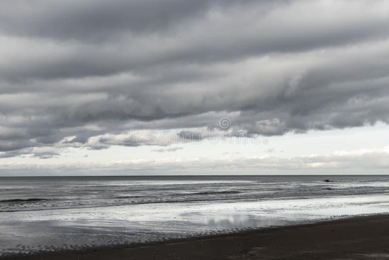 Oostduinkerke, Belgien: Nordsjön med dramatiska moln arkivfoto