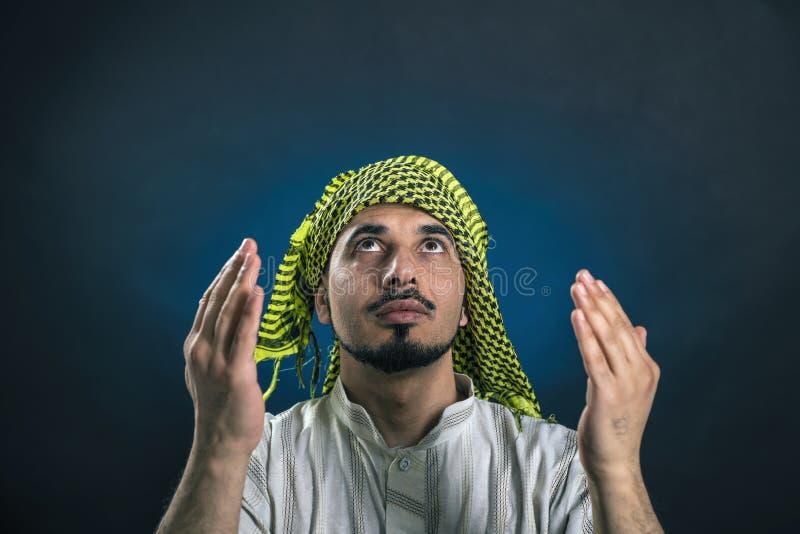 Oostelijk-kijkt mens in traditionele, nationale Arabische kleding kijkt met hoop, die zijn ogen en handen opheffen aan hemel royalty-vrije stock foto