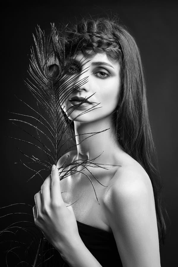 Oostelijke Arabische vrouw met een pauwveer in haar handen dichtbij haar gezicht De make-up Arabische vrouwen van de schoonheidsm stock fotografie