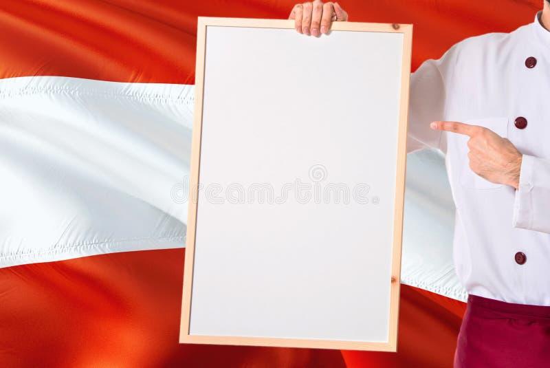Oostenrijkse Chef-kok die leeg whiteboardmenu op de vlagachtergrond van Oostenrijk houden Kok die eenvormige richtende ruimte voo royalty-vrije stock fotografie