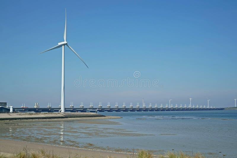 Oosterscheldekering con el molino de viento visto de la orilla de Noord Beveland imagen de archivo libre de regalías
