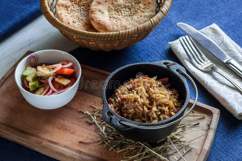Oosterse rijst in een pot met verse groenten en kruiden stock afbeelding