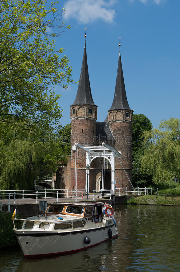 Oostpoort Delft against blue sky showing boat in canal royalty free stock photo