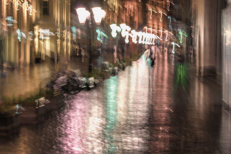Opóźniony wieczór w opustoszałym mieście śpieszą się do domu, osamotneni pedestrians, dżdżysty opóźniony wieczór Jaskrawa ilumina obrazy royalty free