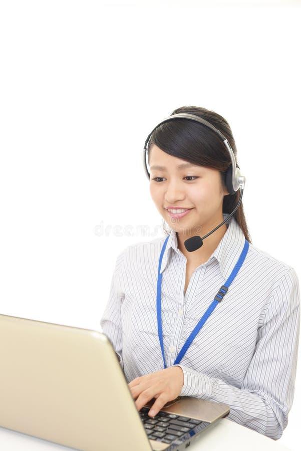 Opérateur de sourire de centre d'attention téléphonique photo stock