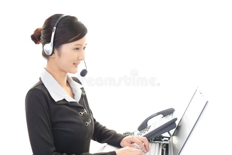 Opérateur de sourire de centre d'attention téléphonique photographie stock libre de droits