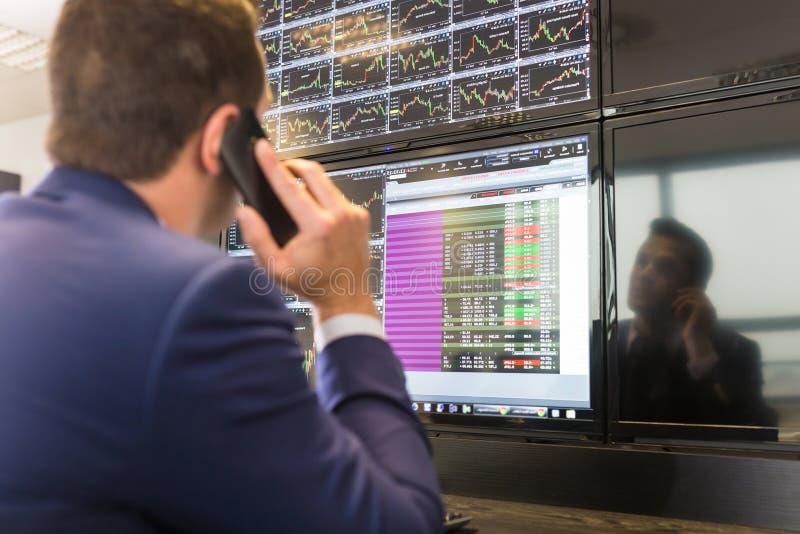 Opérateur en bourse regardant des écrans d'ordinateur photos libres de droits