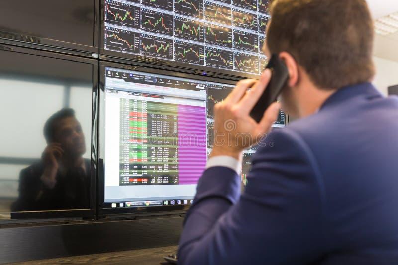 Opérateur en bourse regardant des écrans d'ordinateur images libres de droits