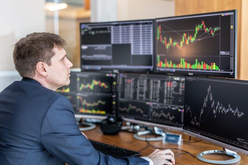 Opérateur en bourse regardant des écrans d'ordinateur dans le bureau trdading photographie stock libre de droits