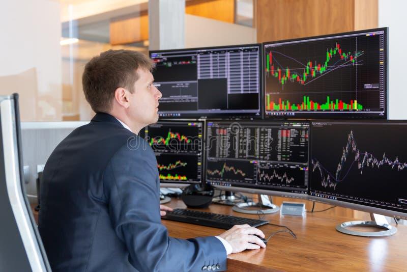 Opérateur en bourse regardant des écrans d'ordinateur dans le bureau trdading photos stock
