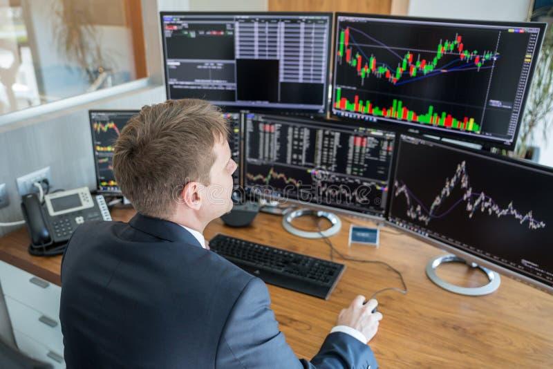 Opérateur en bourse regardant des écrans d'ordinateur dans le bureau trdading images stock
