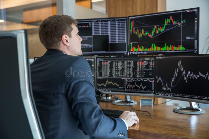Opérateur en bourse regardant des écrans d'ordinateur dans le bureau trdading photo stock