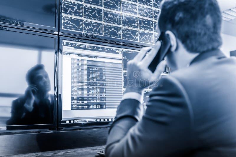 Opérateur en bourse regardant des données du marché sur des écrans d'ordinateur photo libre de droits