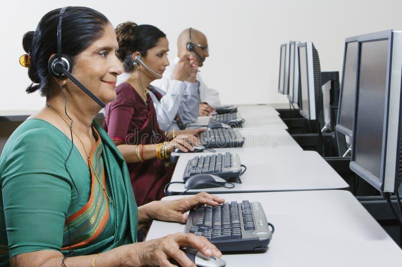 Opérateur féminin de service client travaillant avec des collègues au bureau images libres de droits