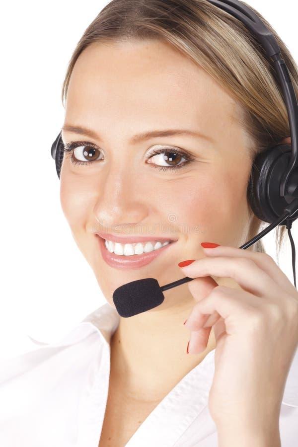 Opérateur gai de sourire de téléphone de support dans l'écouteur photos stock
