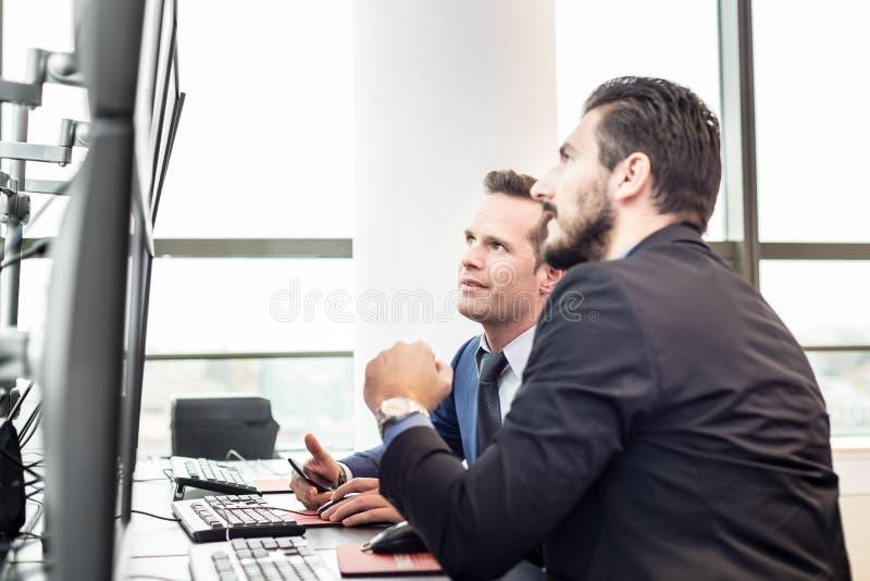 Opérateurs en bourse regardant des données du marché sur des écrans d'ordinateur photographie stock libre de droits