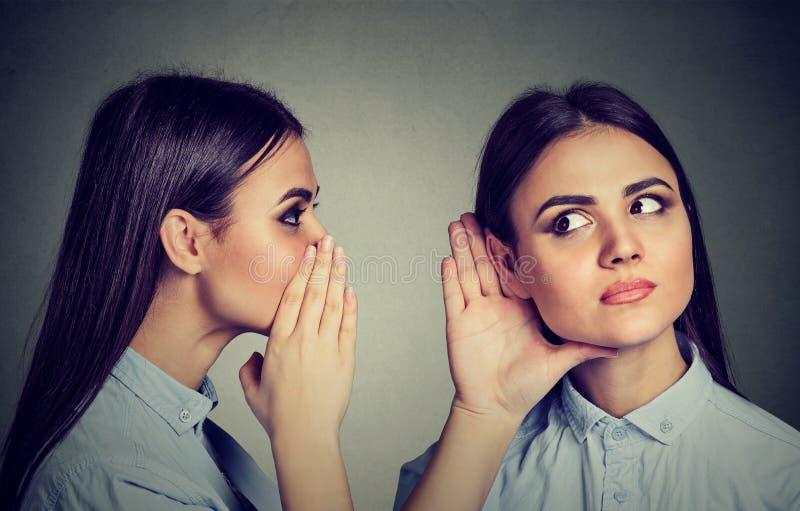 opóźnione plotki Kobieta szepcze w ucho ona fotografia stock
