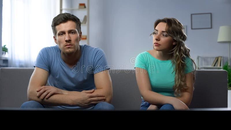 Opõe na família, par olhando a tevê ignorando-se, entendendo mal foto de stock