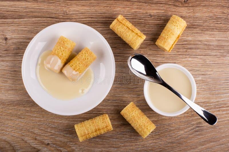 Opłatek rolki z zgęszczonym mlekiem w spodeczku, łyżka na pucharze z zgęszczonym mlekiem, rolki na stole Odgórny widok obrazy stock