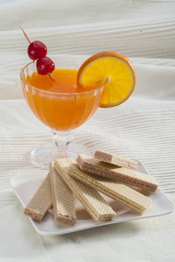 Opłatkowy ciastko z soku pomarańczowego plasterka pomarańczową wiśnią na wykałaczce na bielu talerzu na białym tle obrazy stock