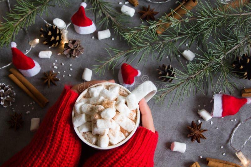 Op άποψη του καυτά φλυτζανιού & marshmallows σοκολάτας στο θηλυκό χέρι που φορά το κόκκινο πουλόβερ, ενάντια στο γκρίζο θέμα υποβ στοκ εικόνες
