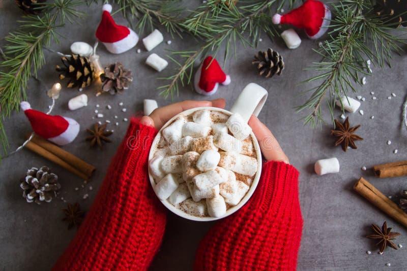 Op взгляд чашки & зефиров горячего шоколада в женской руке нося красный свитер, против серых предпосылки & темы рождества стоковое фото rf