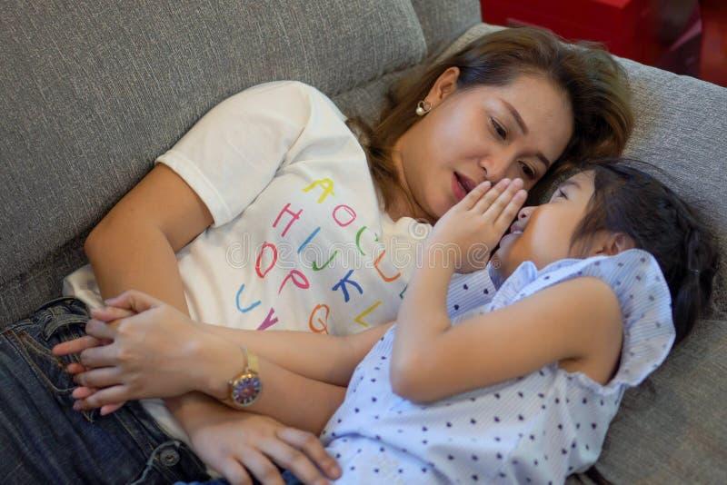 Op bank leggen en moeder en dochter die samen spreken Gelukkige houdende van familie kindmeisje die en Mamma op bed binnen spelen royalty-vrije stock afbeelding