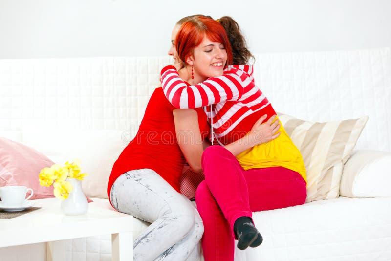 Op bank zitten en gelukkig meisjes die omhelzen stock afbeelding