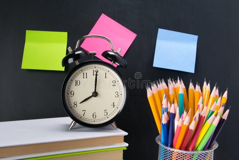 Op de achtergrond van een zwarte Raad met stickers, zijn er een wekker op de boeken en een glas met kleurpotloden stock afbeeldingen
