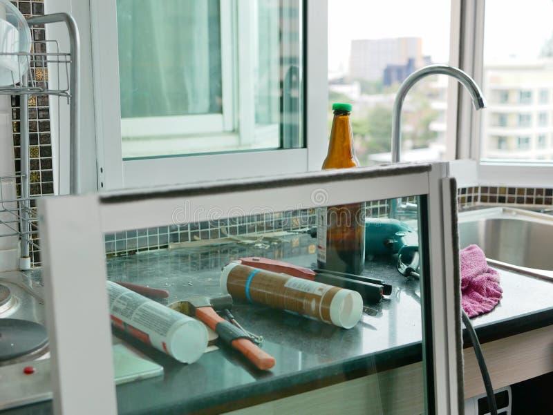 Op-de-gebiedshulpmiddelen en materiaal de technicus die voor glijdende vensterinstallatie gebruiken stock fotografie