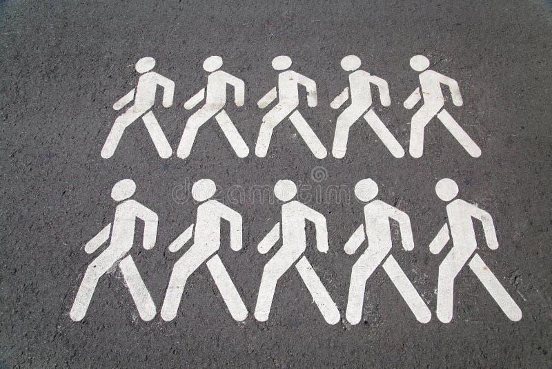 Op de grijze asfaltpictogrammen met het beeld van het lopen mensenwit royalty-vrije stock foto