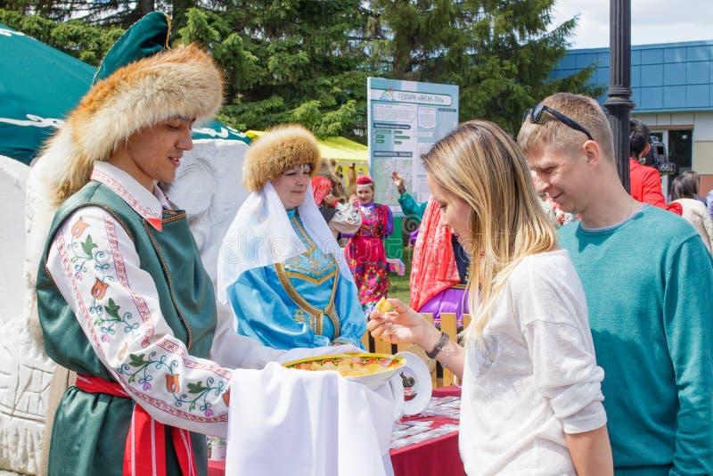 Op de handen van een mensen Bashkir baursak of een Boortsog in een plaat met een etnisch patroon Paar die een traktatie nemen royalty-vrije stock afbeeldingen