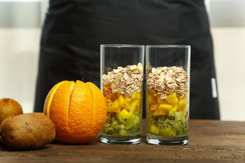 Op de houten lijst zijn twee glazen met stukken van fruit Horizontaal beeld royalty-vrije stock afbeelding