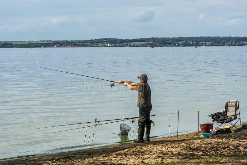 Op de kust van het meer, vist een mens met een hengel royalty-vrije stock foto