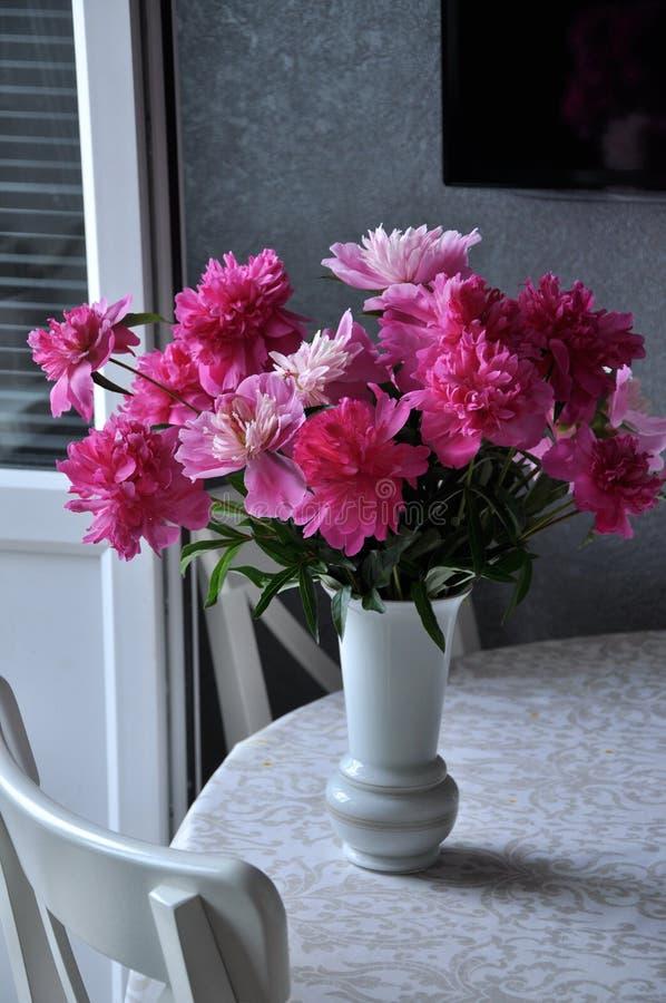 Op de lijst bloemen, pioenen in een vaas stock afbeeldingen