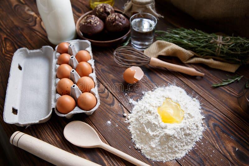 Op de lijst is een dienblad met eieren, bloem met een gebroken ei en keukentoestellen royalty-vrije stock foto's