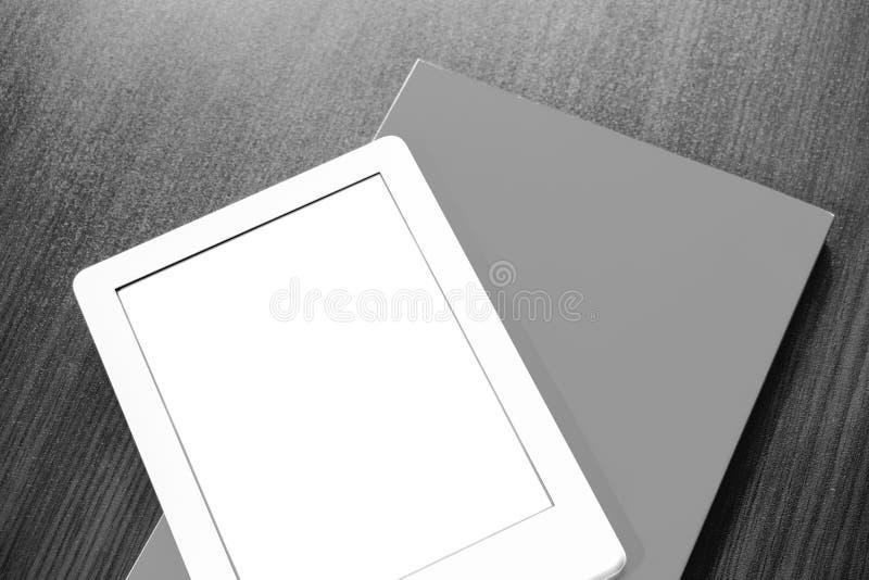 Op de lijst is een een draagbaar e-book en document boek stock foto