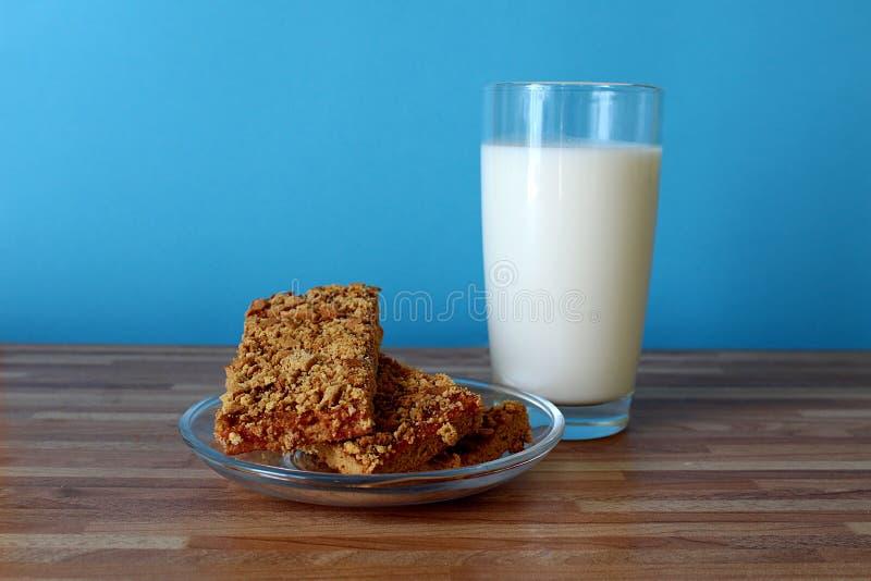 Op de lijst is een glas melk met koekjes stock foto's