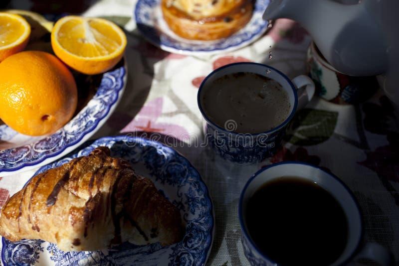 Op de lijst is een koffie, croissant, sinaasappel, thee royalty-vrije stock afbeelding