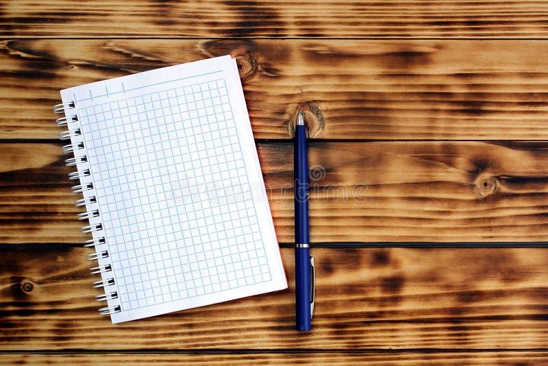 Op de lijst is een notitieboekje in een kooi en een pen royalty-vrije stock foto