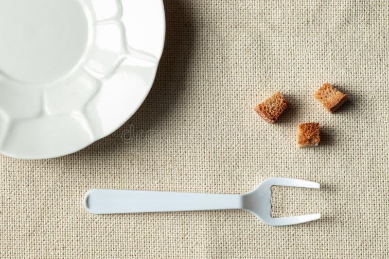 Op de lijst, de lege witte plaat en het liggen naast de crackers Een vork met gebroken middentanden symboliseert vrijwillige diee royalty-vrije stock afbeeldingen