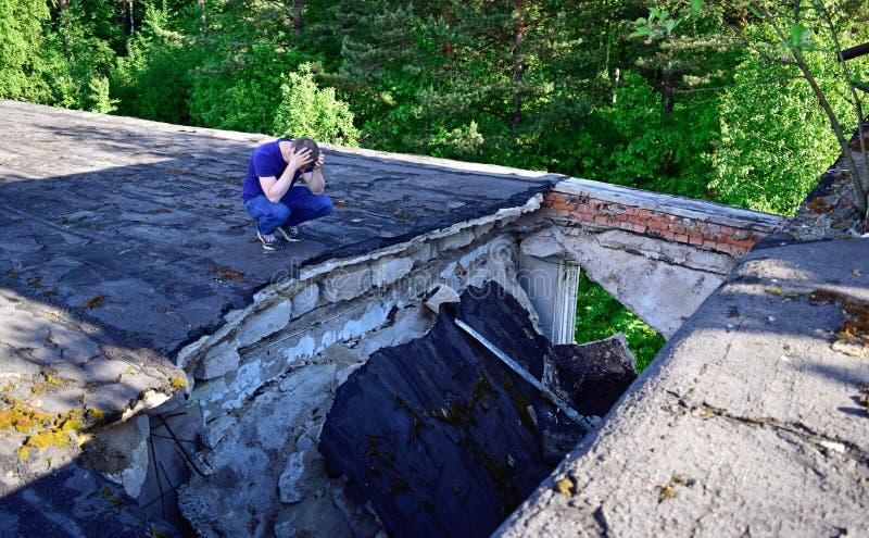 Op de rand van het dak van het vernietigde huis zit een mens stock foto