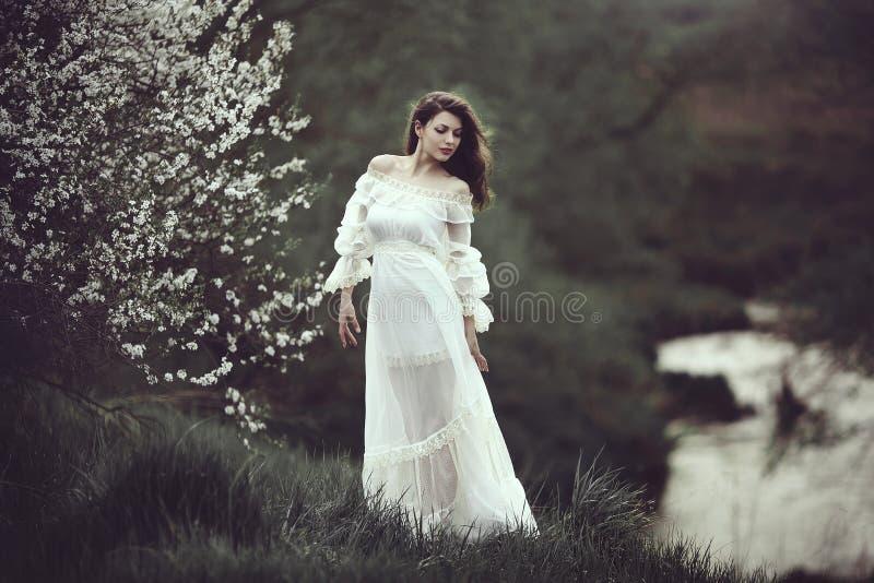 Op de rand van de kust dichtbij de rivier is er een meisje in een witte kleding dichtbij een bloeiende boom Het meisje in de wind stock afbeelding