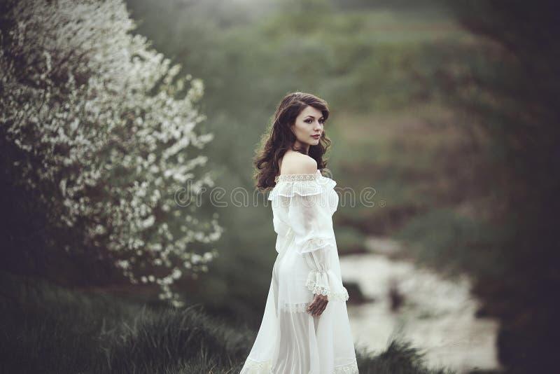 Op de rand van de kust dichtbij de rivier is er een meisje in een witte kleding dichtbij een bloeiende boom Het meisje in de wind royalty-vrije stock foto