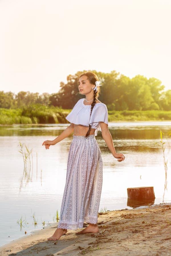 Op de rand van de kust dichtbij de riviertribunes een meisje in een witte kleding stock afbeelding