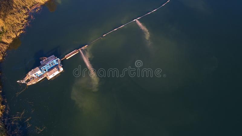 Op de rivier zijn er de werken bij de extractie van zand De werkenbaggermachine royalty-vrije stock foto